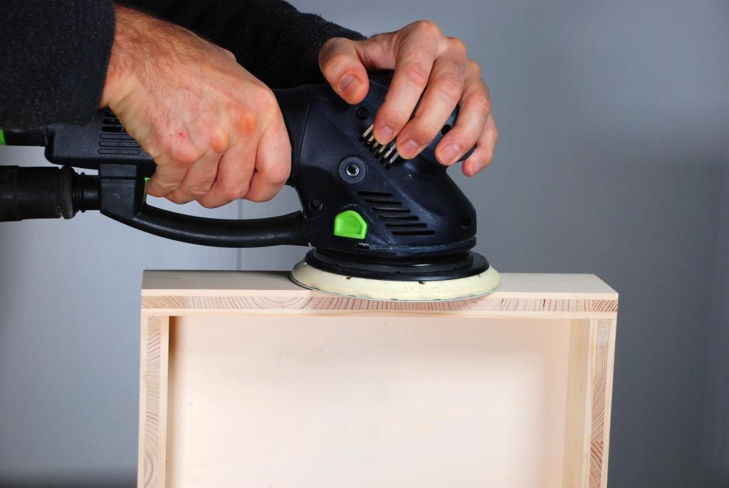 Getriebeexzenterschleifer beim schleifen einer Holzkiste