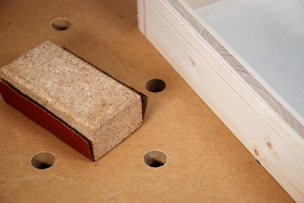 Korkschleifklotz mit Schleifpapier neben Holzkiste